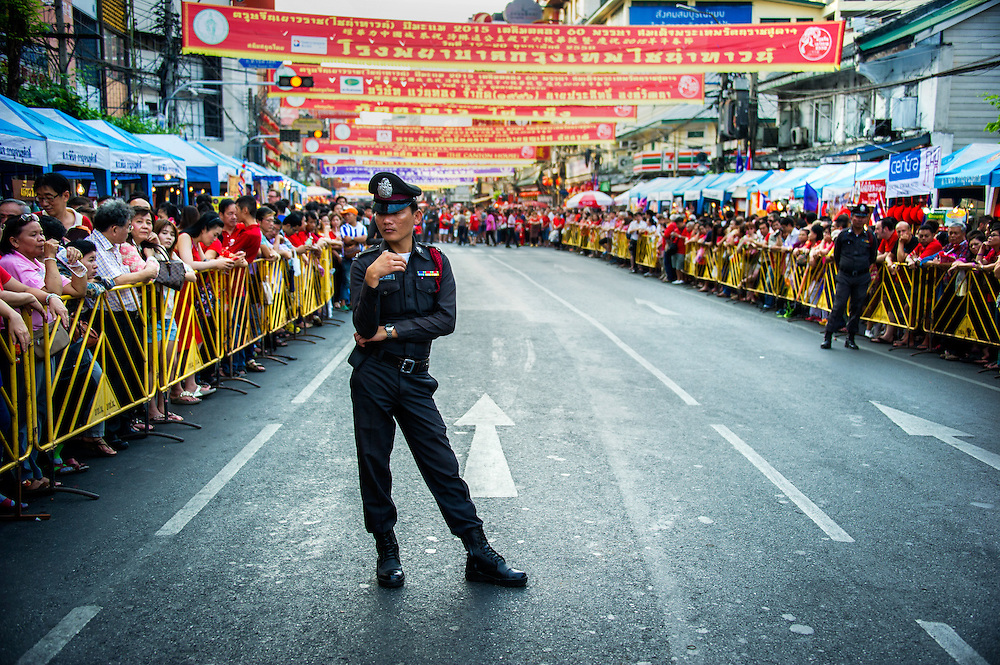Unarmed (which is mandated for royal appearances), a Thai policeman stands security detail for the departure of Princess Sirindhorn's motorcade, at Chinese new year celebrations on Yaowarat road in Bangkok, ‪‎Thailand‬.