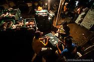 Recibidores y cargadores juegan cartas en el muelle, mientras esperan que llegue las pangas cargadas de calamar durante la madrugada.