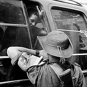A FARC rebel chats with a young passanger at a vehicle checkpoint in the groups zone of control, Caqueta.<br />
