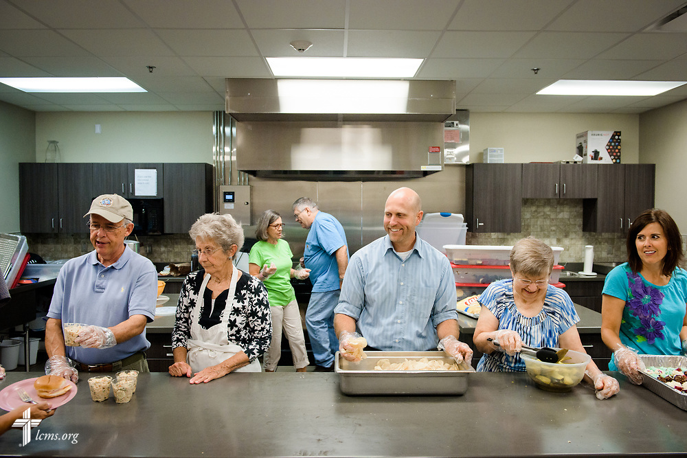 "The Rev. Cory Aker (center), pastor of Faith Lutheran Church, Sioux Falls, SD., serves lunch with fellow volunteers from the parish at the Bishop Dudley Hospitality House homeless shelter on Tuesday, Aug. 1, 2017, in Sioux Falls. The meals are provided by a grant through the ""Stand With Your Community"" program, which was made possible by a partnership between the LCMS, Thrivent Financial and Lutheran Church Extension Fund. LCMS Communications/Erik M. Lunsford"