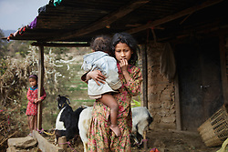Sumitra, 10, holds 11-month-old Kusum, the family's youngest child, while a neighboring child looks on the background. As the oldest daughter, she bears much of the burden of taking care of her younger siblings. <br />