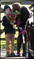 A boy looks on with his flowers as the Duke of Edinburgh walks past him after attending the Church service with the Queen on the Sandringham estate, Sandringham, Norfolk, United Kingdom. Sunday, 29th December 2013. Picture by Andrew Parsons / i-Images