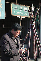 China, Taiyuan, 2007. A fruit seller counts his change towards the end of a long day. Sales are good during Chinese New Year as many people buy fruit for family gifts..