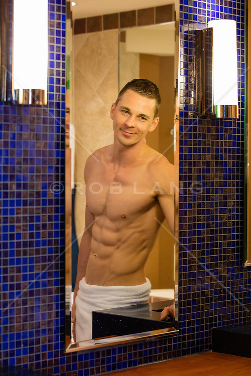 shirtless muscular man in a bathroom mirror