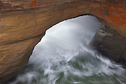 Pacific Ocean waves crash through a sea arch at the entrance to the Devil's Punchbowl, located on the Oregon coast near Depoe Bay.
