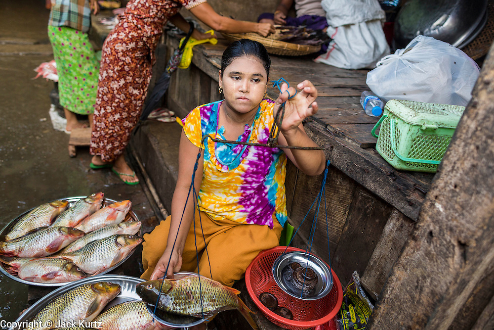 A woman sells fish in the market in Pantanaw, a town in the Irrawaddy Delta (or Ayeyarwady Delta) in Myanmar. The region is Myanmar's largest rice producer, so its infrastructure of road transportation has been greatly developed during the 1990s and 2000s. Two thirds of the total arable land is under rice cultivation with a yield of about 2,000-2,500 kg per hectare. FIshing and aquaculture are also important economically. Because of the number of rivers and canals that crisscross the Delta, steamship service is widely available.