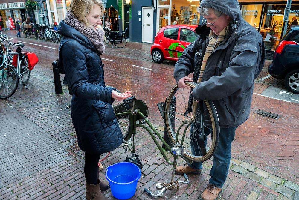 vader plakt band van zijn dochter in de regen. Dochter kijkt toe. Utrecht.