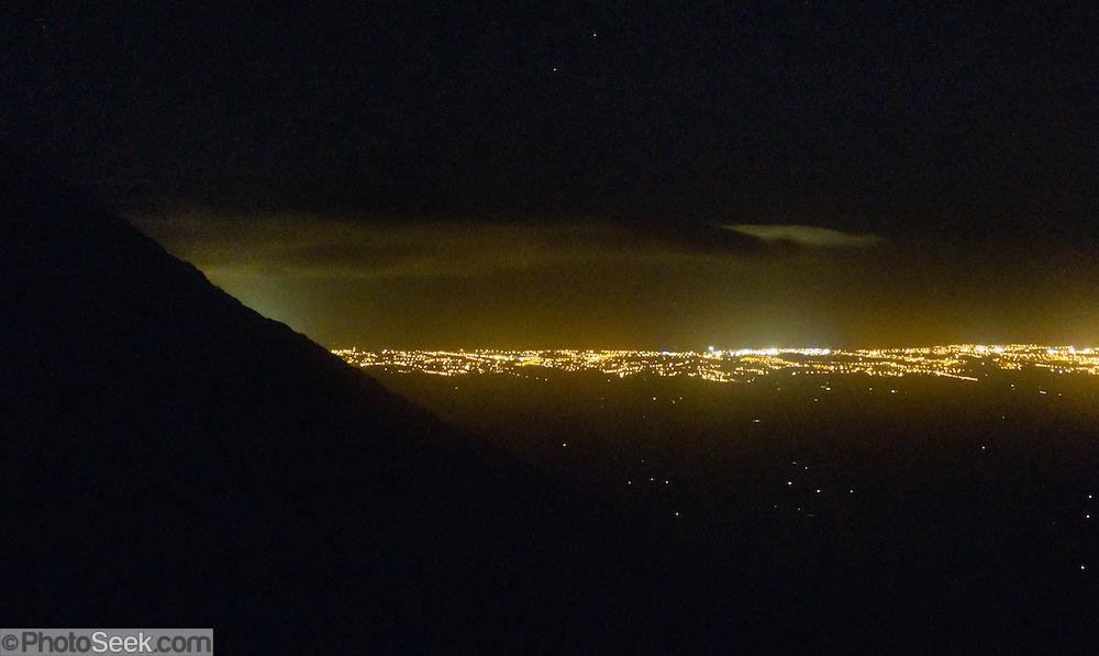 New Plymouth city lights shine below Pouakai Hut on the Pouakai Track, within Taranaki / Mount Egmont National Park, New Zealand, North Island