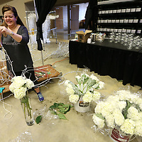 """Junior Auxiliary member Karen Alvarez, of Tupelo, prepares the ballroom table decoration for the Junior Auxiliary Charity Ball that will be held Friday night at the BancorpSouth Arena. The theme for the 55th Annual Charity Ball is """"Once Upon a Time in Tupelo""""."""