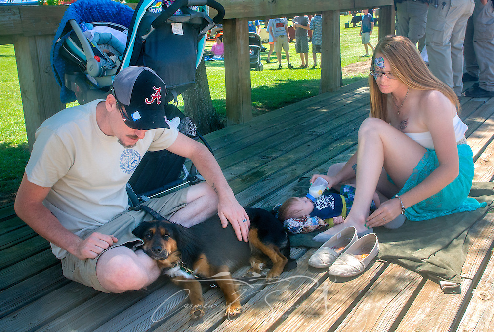 A young family relaxes while waiting for the 66th annual Blessing of the Fleet to begin in Bayou La Batre, Alabama, May 3, 2015. The first fleet blessing was held by St. Margaret's Catholic Church in 1949, carrying on a long European tradition of asking God's favor for a bountiful seafood harvest and protection from the perils of the sea. The highlight of the event is a blessing of the boats by the local Catholic archbishop and the tossing of a ceremonial wreath in memory of those who have lost their lives at sea. The event also includes a land parade and a parade of decorated boats that slowly cruise through the bayou. (Photo by Carmen K. Sisson/Cloudybright)