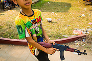 16 MARCH 2013 - NONG SA, LAOS: A boy plays with a toy AK47 made in China at the temple fair at Wat Nong Sa in the village of Nong Sa, which is on Highway 13, in Vientiane province of Laos. The AK47 is the rifle Pathet Lao guerillas carried when they defeated the US backed government in 1975.   PHOTO BY JACK KURTZ