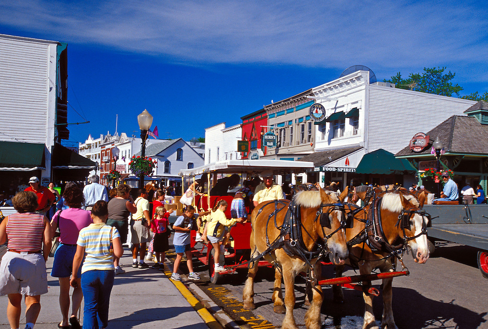 HORSE-DRAWN CARRIAGE TRAFFIC ON THE STREETS OF MACKINAC ISLAND, MICHIGAN WHERE MOTOR VEHICLE TRAFFIC IS PROHIBITED.