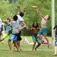 Archer Adams, 8, a third grader at Rakin Elementary School, stretches out to make a catch as he jumps for a Frisbee while playing with his friends at Veterans Park during Rankin's Field Day on Tuesday.