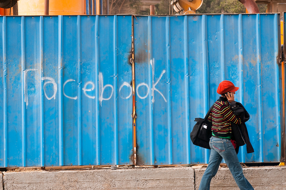 An Egyptian woman walks past a wall with the word Facebook spray painted on it. Facebook was an important communications tool Egyptians used to organize the anti-government demonstrations that brought down the regime of Hosni Mubarak on February 11, 2011. (Cairo, Egypt - February 25, 2011)
