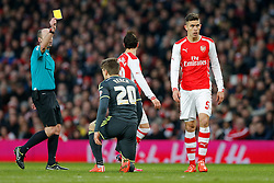 Gabriel Paulista of Arsenal (R) is shown a yellow card by referee Mike Dean - Photo mandatory by-line: Rogan Thomson/JMP - 07966 386802 - 15/02/2015 - SPORT - FOOTBALL - London, England - Emirates Stadium - Arsenal v Middlesbrough - FA Cup Fifth Round Proper.