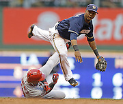 Milwaukee Brewers' Jean Segura, top, forces out Los Angeles Angels' Luis Jimenez and throws to first for a double play on a ball hit by the Angels' Grant Green during the third inning of a baseball game Saturday, Aug. 31, 2013, in Milwaukee. (AP Photo/Jeffrey Phelps)