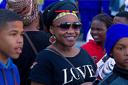A woman wearing a t-shirt with the word 'love' on it stands listening shortly after walking with others during the annual Women's Humanity Walk that takes place yearly on Women's Day. Woman are invited to wear 'doeks' or headdresses appropriate to their culture and to carry a placard showing the name of a woman who has inspired her. This year's walk was an intergenerational celebration of the 60th anniversary of the 1956 Women's March where 20000 women marched on the Union Buildings in Pretoria, South Africa to protest for freedom and justice. Women from all walks of life and all religious and cultural backgrounds marched together in solidarity and in remembrance from the Slave Lodge to the Artscape Theatre in Cape Town, South Africa on the 9th August 2016.<br /> <br /> Photo by:   Mark Wessels / Real Time Images.