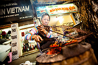 A woman grills shrimp over an open flame on the street in Hanoi, Vietnam.