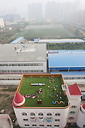 XI\'AN, CHINA - OCTOBER 20: (CHINA OUT)<br /> <br /> Kindergarten Builds Playground On Roof<br /> <br /> Children play on a playground built on the roof of a kindergarten Shaanxi Province of China. The three-story kindergarten reformed its roof into a playground <br /> ©Exclusivepix Media