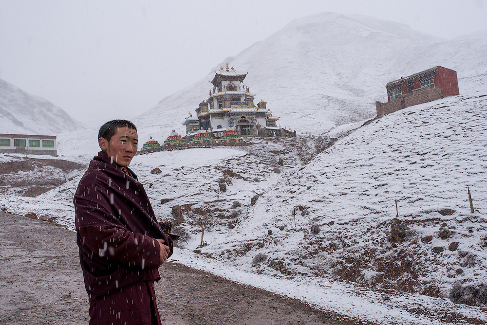 A Buddhist monk stands in the snow outside his monastery in the mountains overlooking Zado, Tibet (Qinghai, China).