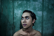 JAKARTA, INDONESIA, MARCH 2013: A young transgender puts make up on in his bedroom at Mami Joyce's house.