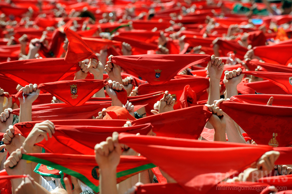 Participants hold traditional red scarves during the 'Chupinazo' to mark the start at noon sharp of the San Fermin Festival on July 6, 2010 in front of the Town Hall of Pamplona, northern Spain. The festival is a symbol of Spanish culture, despite heavy condemnation from animal rights groups, and attracts thousands of tourists to watch the bull runs. PHOTO/Rafa Rivas