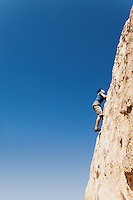 Man Free Climbing on Cliff side view