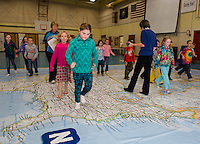 "Belmont Elementary second graders head ""East"" on the interactive map with Phys Ed Teacher Mrs. Nims and Principal Sheila Arnold.  Each class will spend a period during the two days the map is in Belmont.  (Karen Bobotas/for the Laconia Daily Sun)"