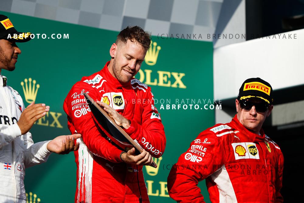 Victorious Ferrari driver Sebastian Vettel of Germany celebrates on the podium during the trophy presentation at the end of the 2018 Rolex Formula 1 Australian Grand Prix at Albert Park, Melbourne, Australia, March 24, 2018.  Asanka Brendon Ratnayake