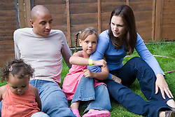 Young family sitting on the grass in the garden together,