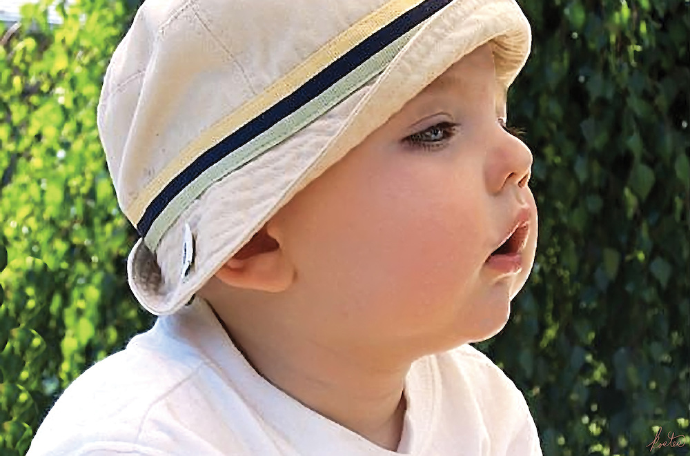 Young child in a hat outside in summer.