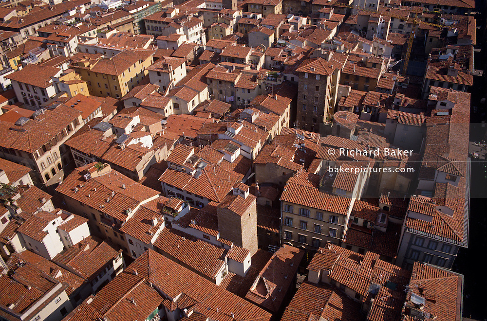 Overlooking tiled rooftops and medival streets from the Duomo in Florence (Firenze) in Italy's Tuscany.