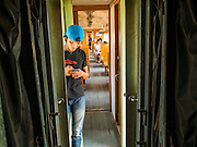 20 MARCH 2015 - KABIN BURI, PRACHINBURI, THAILAND:  A young man checks his smart phone on a 3rd class train headed for Kabin Buri. The State Railways of Thailand (SRT), established in 1890, operates 4,043 kilometers of meter gauge track that reaches most parts of Thailand. Much of the track and many of the trains are poorly maintained and trains frequently run late. Accidents and mishaps are also commonplace. Successive governments, including the current military government, have promised to upgrade rail services. The military government has signed contracts with China to upgrade rail lines and bring high speed rail to Thailand. Japan has also expressed an interest in working on the Thai train system. Third class train travel is very inexpensive. Many lines are free for Thai citizens and even lines that aren't free are only a few Baht. Many third class tickets are under the equivalent of a dollar. Third class cars are not air-conditioned.  PHOTO BY JACK KURTZ