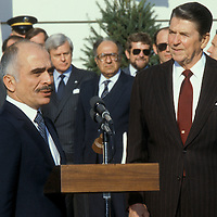 King Hussein of Jordan, Hussein bin Talal, addresses reporters upon his arrival at the  White House on December 20, 1982 with President Ronald Reagan by his side. Also shown is Philip Habib (center, glasses), Special Envoy to the Middle East.