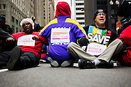 Protestors participate in a sit down protest during a rally on March 27, 2013 protesting the closing of 54 Chicago public schools. Hundreds of teachers, school employees, parents, students and community members came out to the protest the schools closings which are expected to effect more than 30,000 students in the Chicago Public School system.