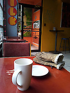Coffee and gloves on table at MILK Coffee Bar, Windsor, Canada.