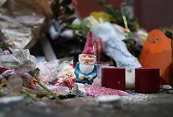 © Licensed to London News Pictures. 12/01/2016. London, UK. A candle in the shape of a gnome sits amongs tributes of flowers, cards and candles placed in front of a mural of David Bowie in Brixton where he was born. Photo credit: Peter Macdiarmid/LNP