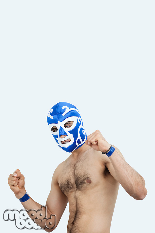 Portrait of a young male wrestler celebrating victory against gray background