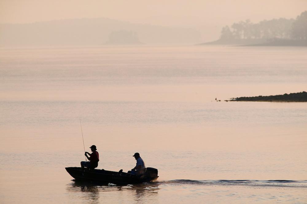 Fisherman heading out at sunrise to go fishing on Lake Ouachita in the Ouachita Mountains of Arkansas