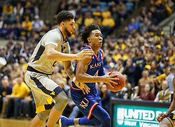Jan 15, 2018; Morgantown, WV, USA; Kansas Jayhawks guard Devonte' Graham (4) drives past West Virginia Mountaineers forward Esa Ahmad (23) during the first half at WVU Coliseum. Mandatory Credit: Ben Queen-USA TODAY Sports