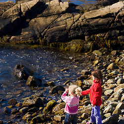 Two girls (ages 4 and 6) play on a cobble beach in Biddeford, Maine.