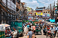 The crowded street, with a large mess of tangled electrical wires on both sides, just outside the Chawri Bazar metro station in Old Delhi, Delhi, India.