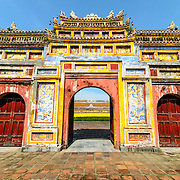 The painted gate to the Dien Tho Residence at the Imperial City in Hue, Vietnam. A self-enclosed and fortified palace, the complex includes the Purple Forbidden City, which was the inner sanctum of the imperial household, as well as temples, courtyards, gardens, and other buildings. Much of the Imperial City was damaged or destroyed during the Vietnam War. It is now designated as a UNESCO World Heritage site.