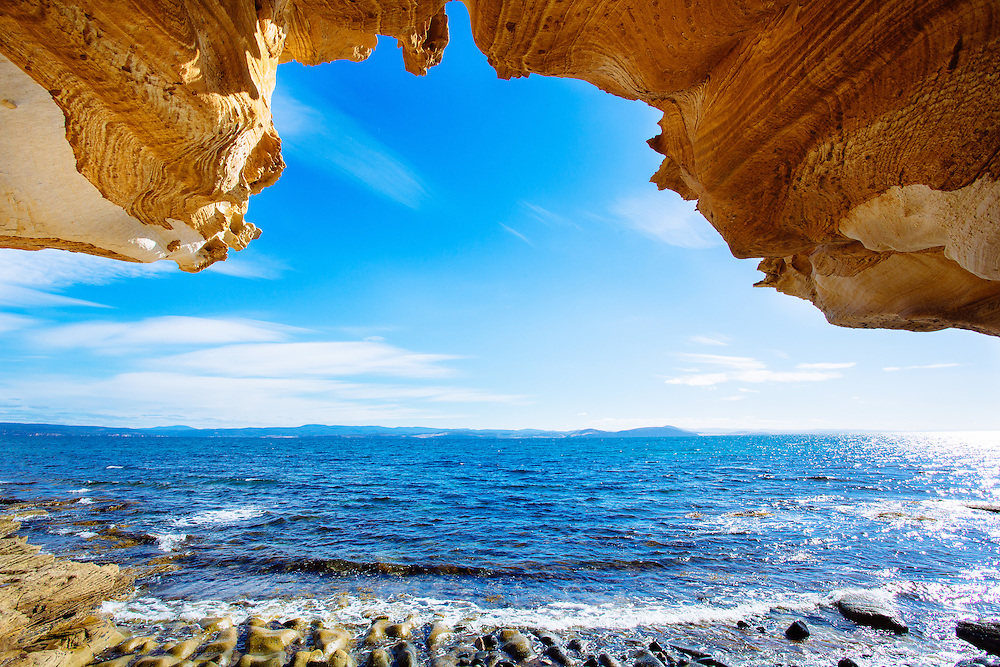 Looking out from underneath the Painted Cliffs towards Triabunna and the mainland of Tasmania. Maria Island National Park.