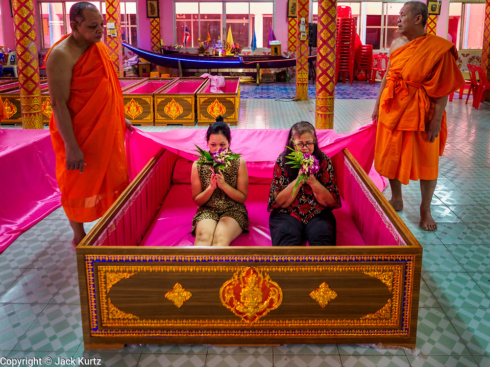 """30 DECEMBER 2017 - BANG KRUAI, NONTHABURI, THAILAND:  People lie in a coffin a resurrection ceremony at Wat Ta Khien, about 45 minutes from Bangkok in Nonthaburi province. The temple is famous for the """"floating market"""" on the canal that runs past the temple and for the """"resurrection ceremonies"""" conducted by monks at the temple. People lie in a coffin and ritualistically die before being reborn. Adherents believe it will improve their karma and help make up for past sins. PHOTO BY JACK KURTZ"""