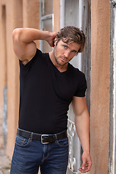 hunky man with big biceps outdoors in a rural town