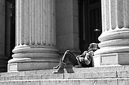 A little sunbathing amid the columns of the main Post Office on 34th street, New York City.