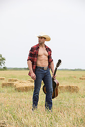 hot cowboy with open shirt holding a guitar in a field