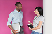 Young man and young woman talking by purple wall