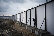 A migrant from Afghanista is seen crossing a construction yard fence in Belgrade makeshift camp. Belgrade, Serbia. March 19th, 2017. Federico Scoppa/CAPTA